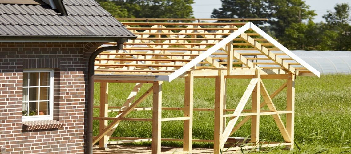 outdoor shot in sunshine. a part from a timber frame construction. outdoors in sunshine. close up of a part of a family home. green landscape in background.On the right side you can see a new wooden scaffolding. here is a growing place